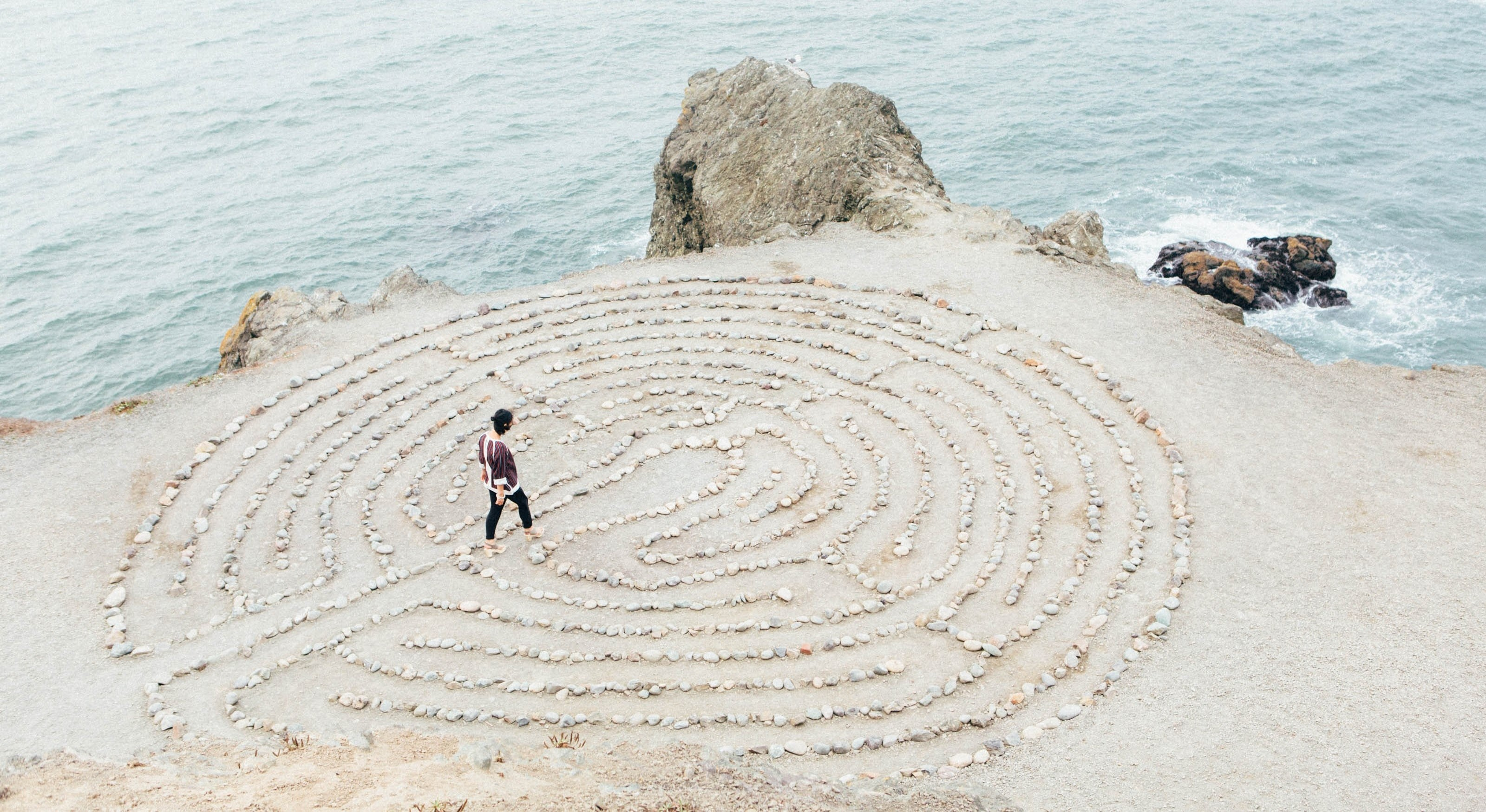 Woman walks a labyrinth on the beach